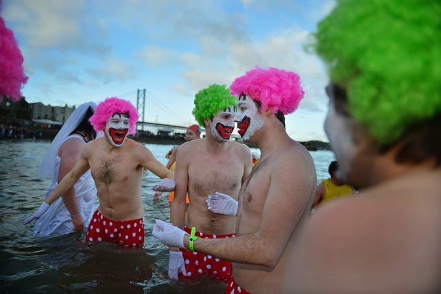 Men dressed as clowns joined over 1,000 New Year swimmers, many in costume, braved freezing conditions in the River Forth in front of the Forth Rail Bridge during the annual Loony Dook Swim on January 1, 2013 in South Queensferry, Scotland. Thousands of people gathered last night to see in the New Year at Hogmanay celebrations in towns and cities across Scotland.  (Photo by Jeff J. Mitchell)