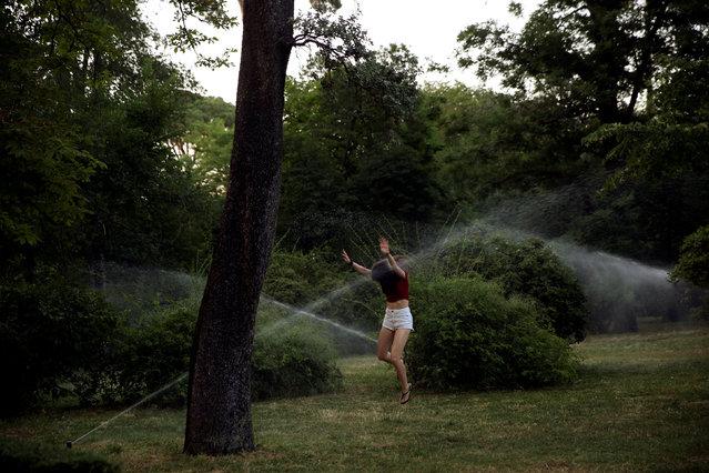 A young girl jumps in between water sprinklers in Retiro park in Madrid, Spain, June 14, 2017. (Photo by Susana Vera/Reuters)