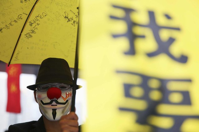 A pro-democracy protester wearing a Guy Fawkes mask holds a yellow umbrella and a banner in the part of Hong Kong's financial central district protesters are occupying November 2, 2014. The former British colony of Hong Kong, which returned to Chinese rule in 1997, has witnessed a month of protests calling on the Beijing-backed government to keep its promise of introducing universal suffrage. (Photo by Damir Sagolj/Reuters)