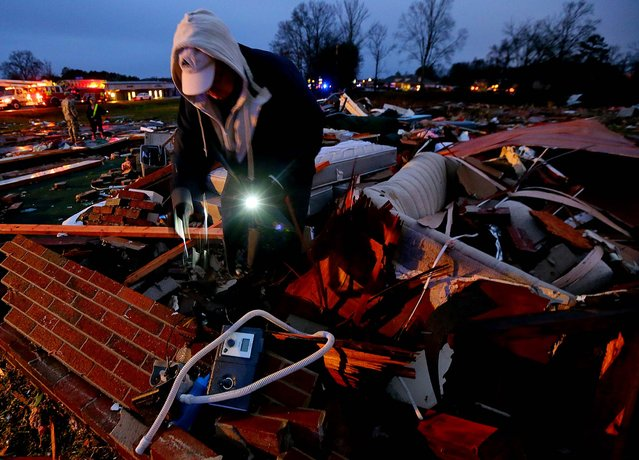 As night falls, Rick Welsh, 63, looks through the remains of his apartment for belongings at the Relax Inn in Adairsville. (Photo by Curtis Compton/Atlanta Journal-Constitution)