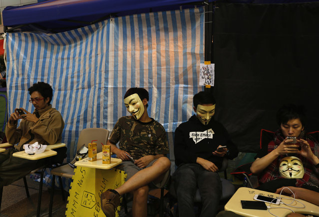 Pro-democracy protesters wearing Guy Fawkes masks rest on a road blocked by Occupy Central in Mongkok shopping district, Hong Kong November 5, 2014. (Photo by Bobby Yip/Reuters)