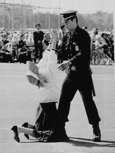 A Seoul policeman attempts to remove a woman who was overcome with emotion during a mass by Pope John Paul II on October 8, 1989 in Seoul's Youido Plaza. An estimated 600,000 people attended the mass. (Photo by Yun Jai-Hyoung/AP Photo)