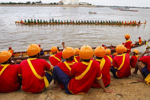 The Royal Palace guards at Tonle Sap river bank watch boatmen rowing their boat in front of Royal Palace in Phnom Penh, Cambodia, Friday, November 7, 2014. The three-day annual festival, started Wednesday, dedicates to the kingdom's ancestral naval warriors. (Photo by Heng Sinith/AP Photo)