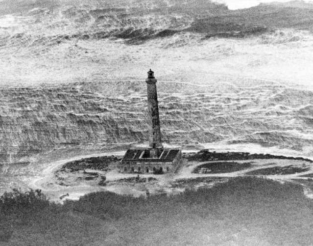 Wind and torrents of rain from hurricane Flora are pictured lashing this lighthouse on Buba's northeast coast as Associated Press staff photographer Jim Kerlin flew over a portion of the island on a flight to hurricane stricken Haiti.  Huge waves at the top of the photo sweep toward the light house at an unknown position on the Cuban coast shown October 9, 1963. (Photo by Jim Kerlin/AP Photo)