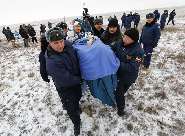 Ground personnel carry International Space Station (ISS) crew member Alexander Gerst of Germany shortly after landing near the town of Arkalyk in northern Kazakhstan, November 10, 2014. (Photo by Shamil Zhumatov/Reuters)