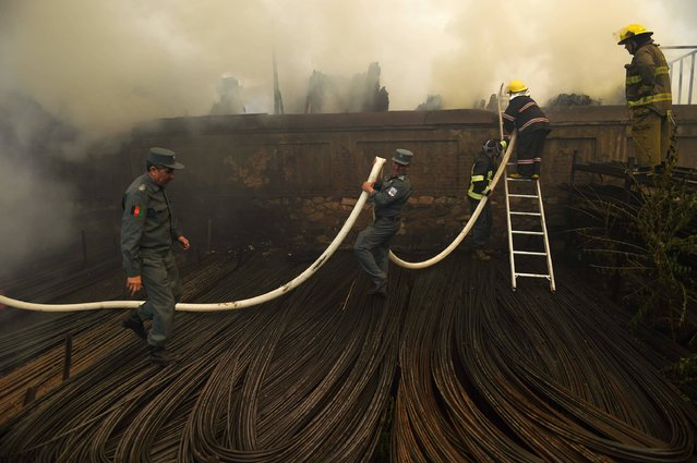 Afghan firefighters try to extinguish a fire at a wood market at Quwai Markaz in Kabul on September 18, 2016. A fire that broke out at a wood market in Kabul has caused heavy losses for shopkeepers. The cause of the fire is unknown. (Photo by Wakil Kohsar/AFP Photo)