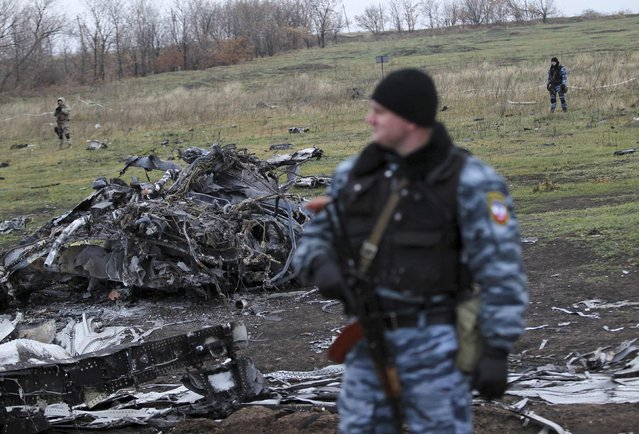 A pro-Russian armed man secures crash site wreckage of the Malaysia Airlines Boeing 777 plane (flight MH17) at the site of the plane crash near the settlement of Grabovo in the Donetsk region November 16, 2014. Local emergency services have begun collecting parts of the wreckage from its crash site in the middle of the conflict zone, Dutch air accident investigators said on Sunday. (Photo by Antonio Bronic/Reuters)