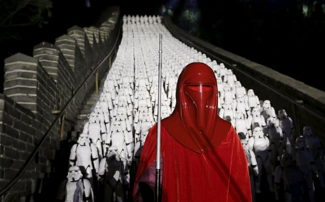 """A fan dressed as an Imperial Royal Guard character from """"Star Wars"""" poses for a photo in front of five hundred replicas of Stormtroopers at the Juyongguan section of the Great Wall of China during a promotional event for """"Star Wars: The Force Awakens"""" film, on the outskirts of Beijing, China, October 20, 2015. (Photo by Jason Lee/Reuters)"""