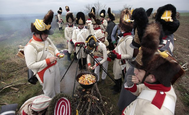 Historical re-enactment enthusiasts dressed as soldiers cook near the southern Moravian village of Herspice November 28, 2014. Hundreds of history enthusiasts gathered near the city of Slavkov before a re-enactment of Napoleon's famous battle of Austerlitz on Saturday to mark its 209th anniversary. (Photo by David W. Cerny/Reuters)