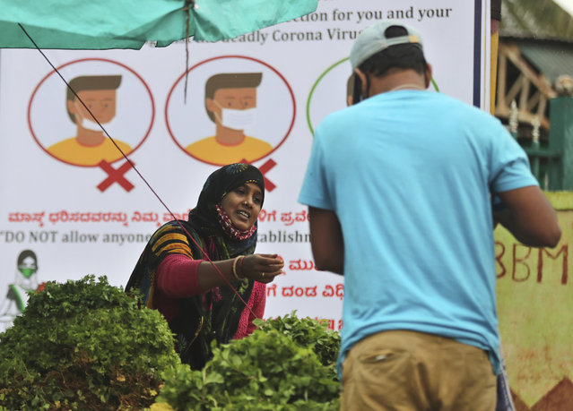 An Indian vegetable vendor wearing a face mask around her neck interacts with a customer in front of a hoarding informing people about proper use of masks in Bengaluru, India, Sunday, October 11, 2020. India's confirmed coronavirus toll crossed 7 million on Sunday with a number of new cases dipping in recent weeks, even as health experts warn of mask and distancing fatigue setting in. (Photo by Aijaz Rahi/AP Photo)