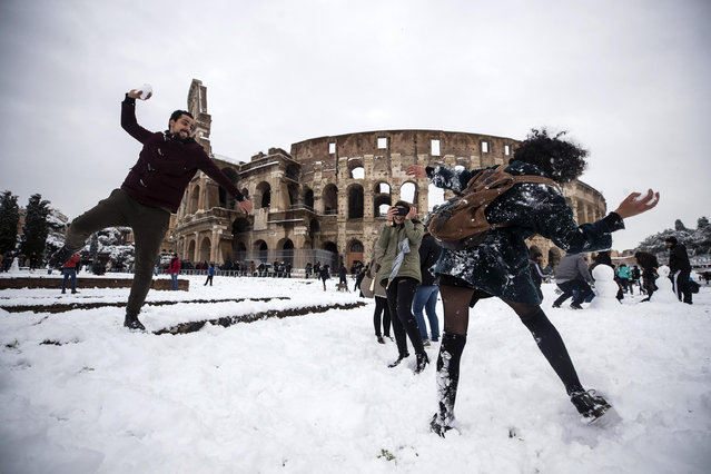 People take part in a snowball fight in front of the Colosseum covered by snow during a snowfall in Rome, Italy, 26 February 2018. Media reports on 26 February state that extreme cold weather is forecast to hit many parts of Europe with temperatures plummeting to a possible ten year low. (Photo by Angelo Carconi/EPA/EFE)