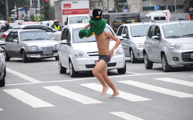 A boy crosses Avenida Paulista, São Paulo, only in underwear and a mask of crocodile head, on March 20, 2013. (Photo by J. Duran Machfee/Futura Press/Estadão Conteúdo)