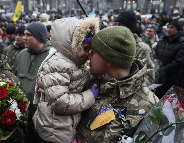 "A serviceman of ""Kiev 12"" military defence battalion embraces his daughter as he attends a welcoming ceremony in central Ukrainian capital Kiev December 6, 2014. (Photo by Gleb Garanich/Reuters)"