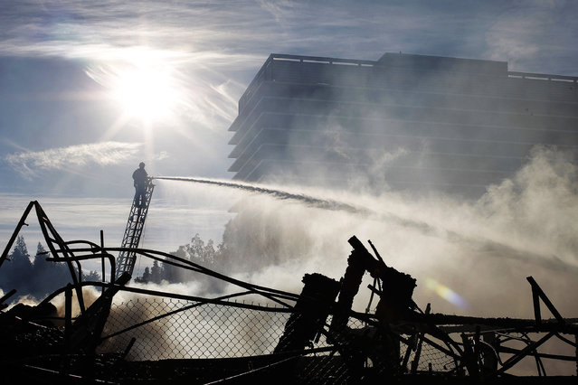 Firefighters hose down the smoldering ruins of a seven-story apartment building under construction alongside the 110 freeway that was destroy in an early morning fire on December 8, 2014 in Los Angeles, California. The fire also damaged nearby high-rise buildings and shut down freeways, causing massive traffic problems for morning commuters. (Photo by David McNew/Getty Images)