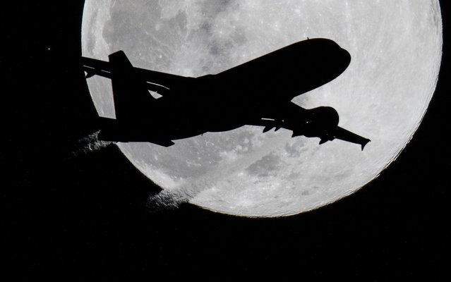 An aircraft approaches Frankfurt Airport, Germany on March 20, 2019, before the full moon for its landing approach. Dry weather in the coming days should also provide a clear view of the sky at night. (Photo by Boris Roessler/dpa)