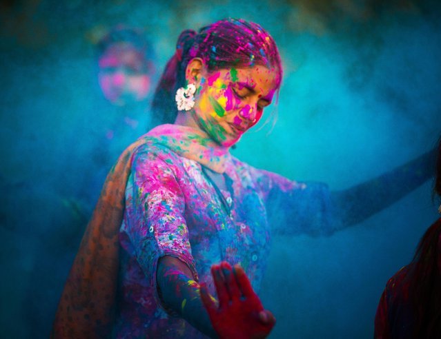 Holi Festival in India. Young woman dancing around blue powder while celebrating the Indian Holi Day. (Photo by THEPALMER/Getty Images)
