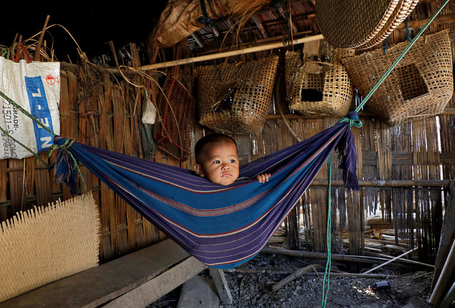 Tina Chakma, a six-month-old baby girl plays in an improvised hammock inside her parents' house on the outskirts of Agartala, India, March 20, 2018. (Photo by Jayanta Dey/Reuters)