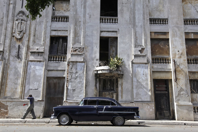 A 1955 Chevrolet is parked near an abandoned building in Havana, April 8, 2010. (Photo by Enrique De La Osa/Reuters)