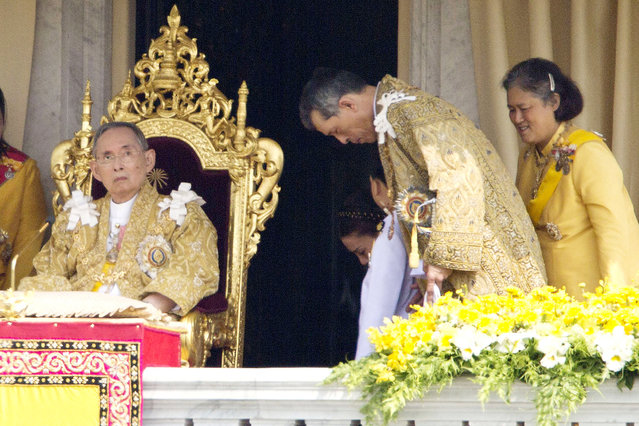 In this December 5, 2012, file photo, Thailand's King Bhumibol Adulyadej, left, is seated as Crown Prince Vajiralongkorn, second left, and Princess Sirindhorn, right, stand after he addressed the crowd from a balcony of the Ananta Samakhom Throne Hall on his 85th birthday in Bangkok. (Photo by Wason Wanichakorn/AP Photo)