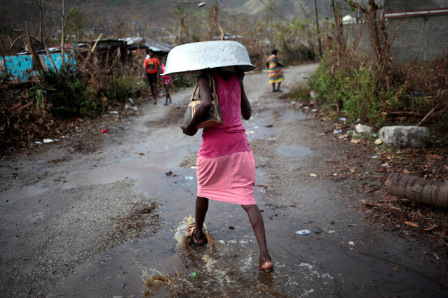 A woman walks protecting herself from rain after Hurricane Matthew in Les Anglais, Haiti, October 13, 2016. (Photo by Andres Martinez Casares/Reuters)