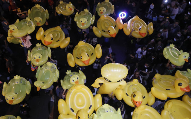 Inflatable yellow ducks, which have become good-humored symbols of resistance during anti-government rallies, are lifted over a crowd of protesters Friday, November 27, 2020 in Bangkok, Thailand. (Photo by Sakchai Lalit/AP Photo)