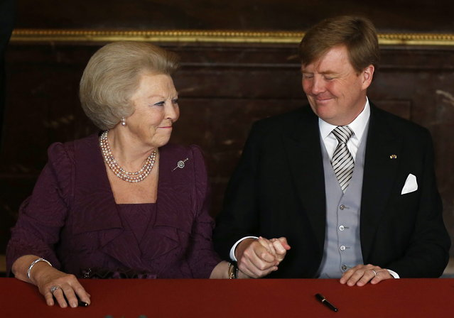 Dutch Princess Beatrix, left, clasps the hand of her son, King Willem-Alexander, after the Act of Abdication was signed to end her reign as Monarch, in the Mozeszaal or Mozes hall of the Royal Palace in Amsterdam, The Netherlands, Tuesday April 30, 2013. Around a million people are expected to descend on the Dutch capital for a huge street party to celebrate the first new Dutch monarch in 33 years. (Photo by Bart Maat/AP Photo)