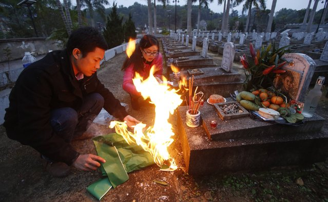 Thiem Nguyen (L) and his sister-in-law Kim Chi Tran burn paper replica of cloth, money and incenses in front of a tomb, which they believe belongs to their relative, captain Pham Hoa Lu, on the 70th founding anniversary of the Vietnam People's Army, at the Viet-Laos cemetery in the border district of Anh Son December 22, 2014. Lu was killed by a U.S. bomb in Laos on December 19, 1971, according to the Vietnamese Defence Ministry. (Photo by Reuters/Kham)