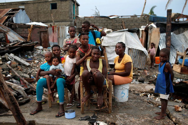 Neighbors pose for a photo next to their destroyed houses after Hurricane Matthew hit Jeremie, Haiti, October 16, 2016. (Photo by Carlos Garcia Rawlins/Reuters)