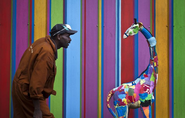 In this photo taken Monday, April 29, 2013, carver Jackson Mbatha, 40, poses next to a an unfinished large toy giraffe he is making from pieces of discarded flip-flops, in front of a painted workshop wall at the Ocean Sole flip-flop recycling company in Nairobi, Kenya. The company is cleaning the East African country's beaches of used, washed-up flip-flops and the dirty pieces of rubber that were once cruising the Indian Ocean's currents are now being turned into colorful handmade giraffes, elephants and other toy animals. (Ben Curtis/AP Photo)