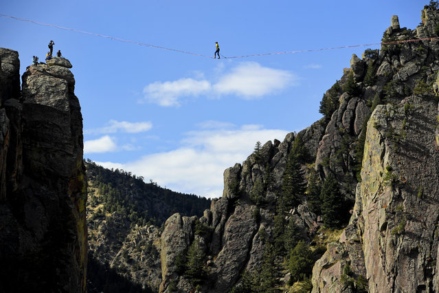 In this Saturday, October 15, 2016, photo, Taylor VanAllen, 24, makes the FA, or First Across, on a high-line from the Wind Tower rock formation to the Bastille rock formation, 450 feet off the ground, in Boulder, Colo. VanAllen, an athlete with Slackline Industries, recreated the Ivy Baldwin high line crossing of Eldorado Canyon in a benefit for trail building at the state park. (Photo by Helen H. Richardson/The Denver Post via AP Photo)