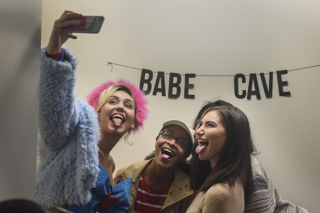 Singer, songwriter, actress and philanthropist Miley Cyrus, L, takes a selfie while doing her signature tongue-out pose with GMU students Samaria Moss, 18, C, of Spottsylvania, VA, Jaide Tarwid, 18, from Wisconsin, and Zimuzo Okala, 19, of Chesapeake, VA, (blocked) as Cyrus makes a campaign visit for Hillary Clinton and Tim Kaine in Northern Virginia at George Mason University on Saturday, October 22, 2016 in Fairfax, VA. (Photo by Jahi Chikwendiu/The Washington Post)