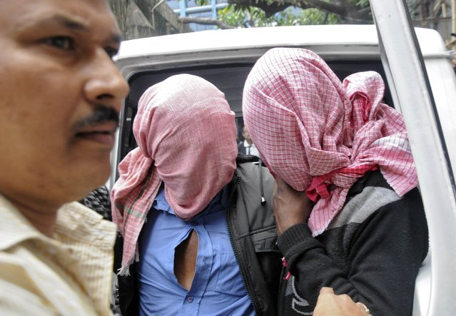 A plain-clothes policeman (L) escorts two men who were arrested in connection with the alleged abduction and gang-rape of a Japanese tourist, outside a court in Kolkata January 3, 2015. Indian police have arrested five men in connection with the alleged abduction and gang-rape of a 23-year-old Japanese tourist, officials said on Saturday. (Photo by Reuters/Stringer)