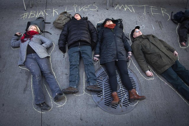 """Demonstrators stage a """"die in"""" in front of News Corporation's New York office in Manhattan January 2, 2015. (Photo by Carlo Allegri/Reuters)"""