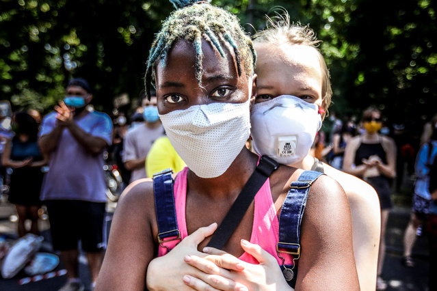 A participant embraces another at a Black Lives Matter (BLM) demonstration in Berlin, Germany, 27 June 2020. A large crowd gathered under the German capital's Victory Column Siegessaeule in protest against racism and in commemoration of the death of George Floyd, an African-American man who died while in Minneapolis police custody on 25 May 2020 after the arresting officer knelt on his neck for more than 8 minutes. (Photo by Omer Messinger/EPA/EFE)
