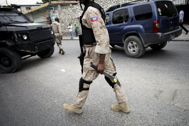 A National Police officer carries a confiscated machete during a demonstration against the results of the presidential elections in Port-au-Prince, Haiti, November 26, 2015. (Photo by Andres Martinez Casares/Reuters)