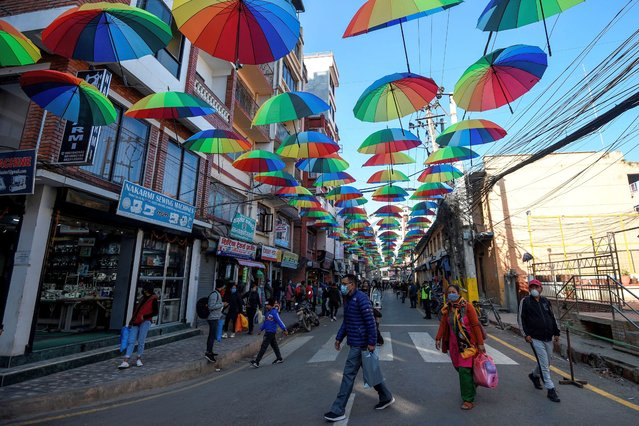 Residents wearing a facemask to contain the spread of the Covid-19 coronavirus, walk along a street decorated with umbrellas, in Kathmandu on December 17, 2020. (Photo by Prakash Mathema/AFP Photo)