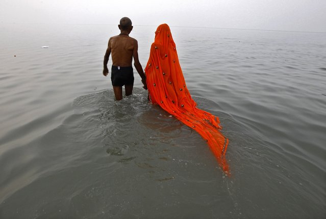Hindu pilgrims prepare to take a dip at the confluence of the Ganges river and the Bay of Bengal on the occasion of Makar Sankranti festival at Sagar Island, south of Kolkata January 14, 2015. Makar Sankranti is an auspicious festival celebrated by Hindus across the country that marks the start of the harvest season. (Photo by Rupak De Chowdhuri/Reuters)