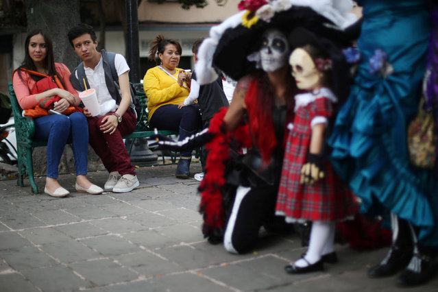 "People watch participants, whose faces are painted as popular Mexican figure ""Catrina"", during the annual Catrina Fest, part of Day of the Dead celebrations, in Mexico City, Mexico, November 2, 2016. (Photo by Edgard Garrido/Reuters)"