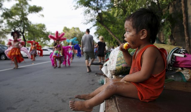 A homeless child watches a parade by transgender women and government health workers during a World Aids day celebration in Manila, Philippines, December 1, 2015. (Photo by Erik De Castro/Reuters)
