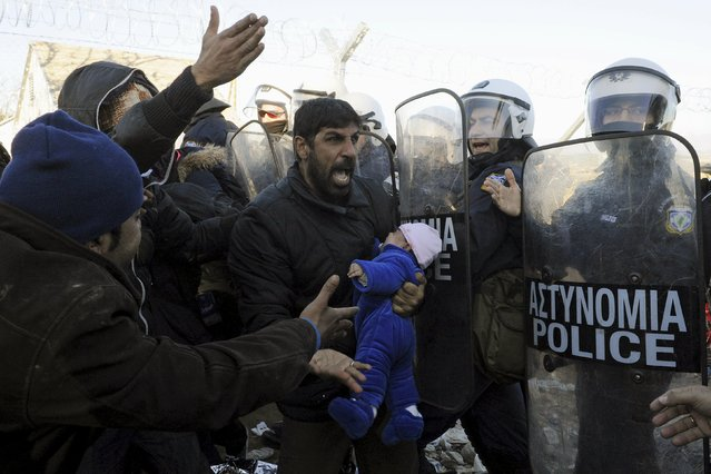 A stranded migrant holding a baby shouts next to a Greek police cordon following scuffles at the Greek-Macedonian border, near the village of Idomeni, Greece, December 3, 2015. (Photo by Alexandros Avramidis/Reuters)