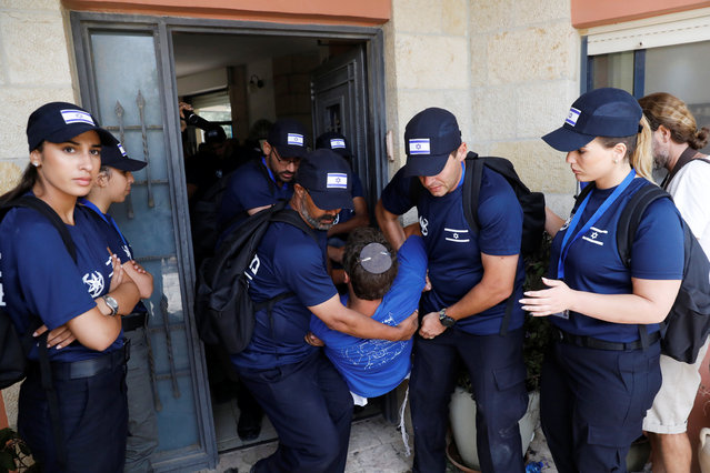 Israeli security forces carry a man out of a house during the evacuation of Jewish settler families from the illegal outpost of Netiv Ha'avot in the occupied West Bank on June 12, 2018. (Photo by Ronen Zvulun/Reuters)