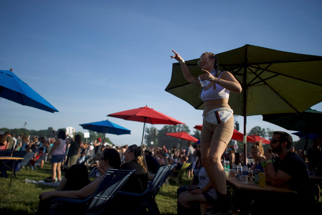A woman dances on a picnic table as Lil Wayne performs on the third day of the Firefly Music Festival in Dover, Delaware U.S., June 16, 2018. (Photo by Mark Makela/Reuters)