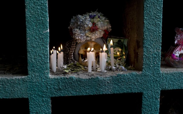 """A decorated human skull or """"natitas"""", is illuminated by candlelight during the Natitas Festival celebrations, in La Paz, Bolivia, Tuesday, November 8, 2016. (Photo by Juan Karita/AP Photo)"""