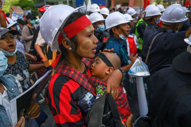 A protester carries a child march during a demonstration against the February 1 military coup in Yangon on February 10, 2021. (Photo by Ye Aung Thu/AFP Photo)