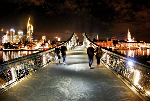 "People walk over a small bridge over the river Main called ""Eiserner Steg"" in Frankfurt, Germany, late Sunday, November. 6, 2016. (Photo by Michael Probst/AP Photo)"