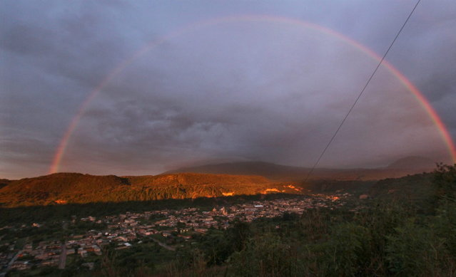 A rainbow forms over the town of Santiago Xalizintla where the Popocatepetl volcano, behind center, is covered by clouds in Mexico, Monday, July 8, 2013. The Environment Ministry has urged residents to take preventive measures to deal with the ash, including wearing dust masks, covering water supplies and staying indoors as needed. (Photo by Marco Ugarte/AP Photo)