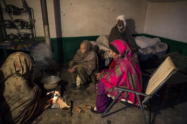 A family sits around a wood fire while waiting for tea to brew at their house on Margalla Hills in Islamabad January 22, 2015. (Photo by Zohra Bensemra/Reuters)
