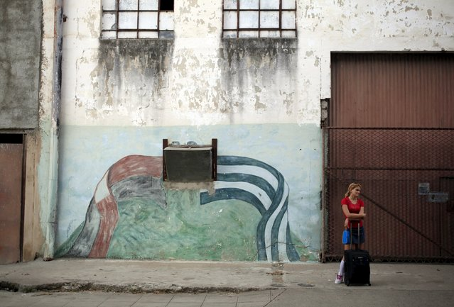 A student stands near graffiti of the colours of Fidel Castro's 26th of July Movement (L) and the Cuban flag (R) in Vertientes, Camaguey province November 13, 2015. (Photo by Enrique de la Osa/Reuters)