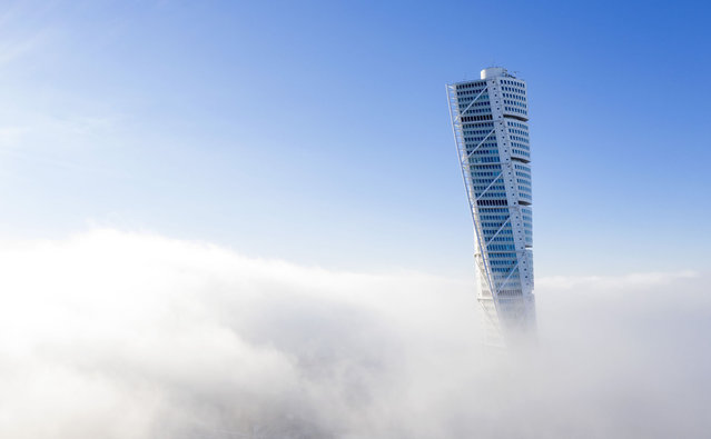 The Turning Torso scyscraper in Malmo, Sweden is surrounded by sea smoke on November 27, 2020. (Photo by Johan Nilsson/TT News Agency/AFP Photo)