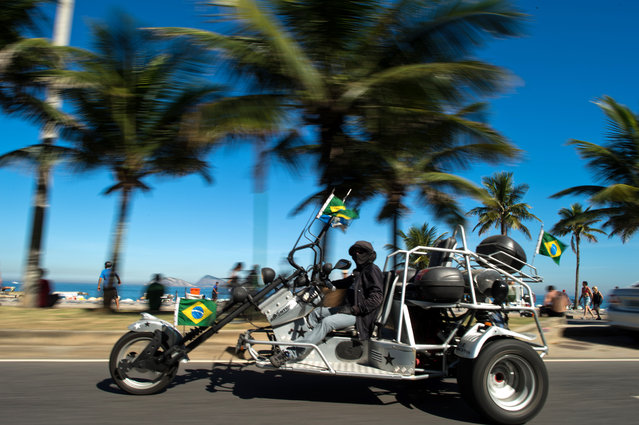 A man wearing a keffiyeh and listening to arab music rides his motobike adorned with Brazilian flags along the Ipanema Beach seafront in Rio de Janeiro, Brazil on July 07, 2013. (Photo by Christophe Simon/AFP Photo)